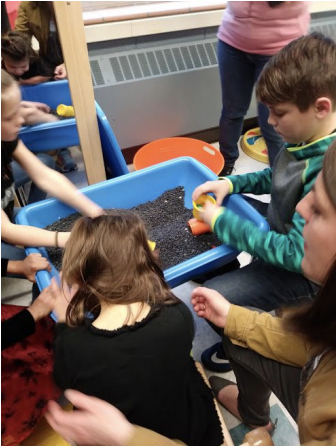 Children sitting on the floor with their hands exploring items in dirt in a plastic blue rectangular container.