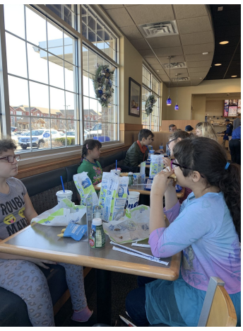 Students sitting around a restaurant table eating lunch.