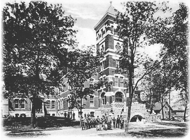 Old main brick building with a large tower and surrounded by grass and trees. Several children playing outside in front of building.