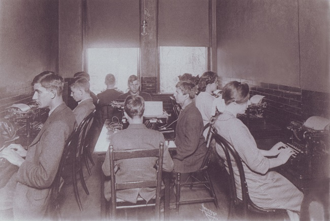 Children in a room sitting in chairs and typing on old typewriters. Boys are wearing suits and girls wearing dresses.