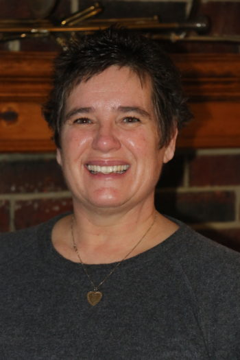 A Head Shot Of A Female With Short Brown Hair Who Is The Director Of Field Services Standing In Front Of Dark Brick Wall Wearing A Dark Green Shirt And A Gold Necklace.