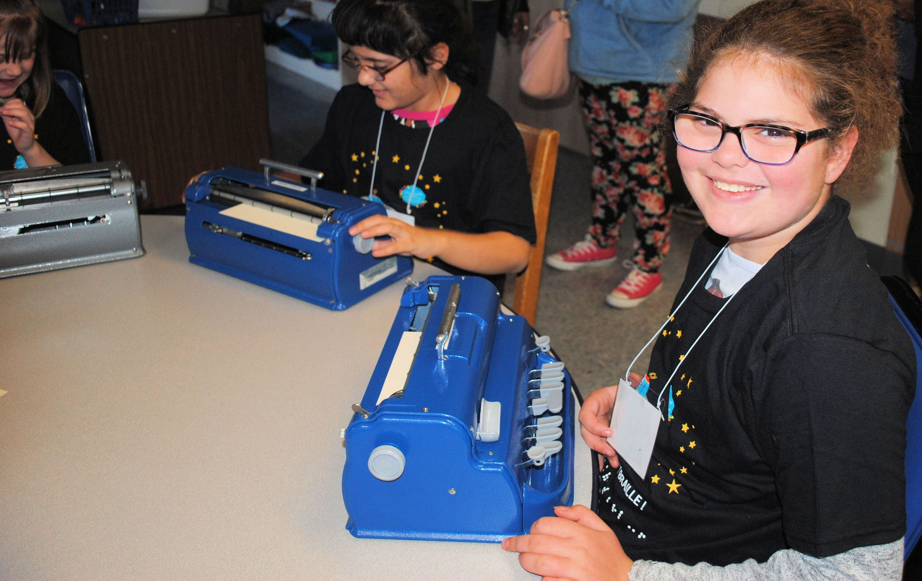 Student Sitting At A Table, Looking At Camera With A Large Smile. Her Braille Writer Is On The Table.