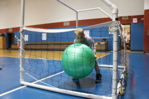 Student with a large green ball inside a soccor net.