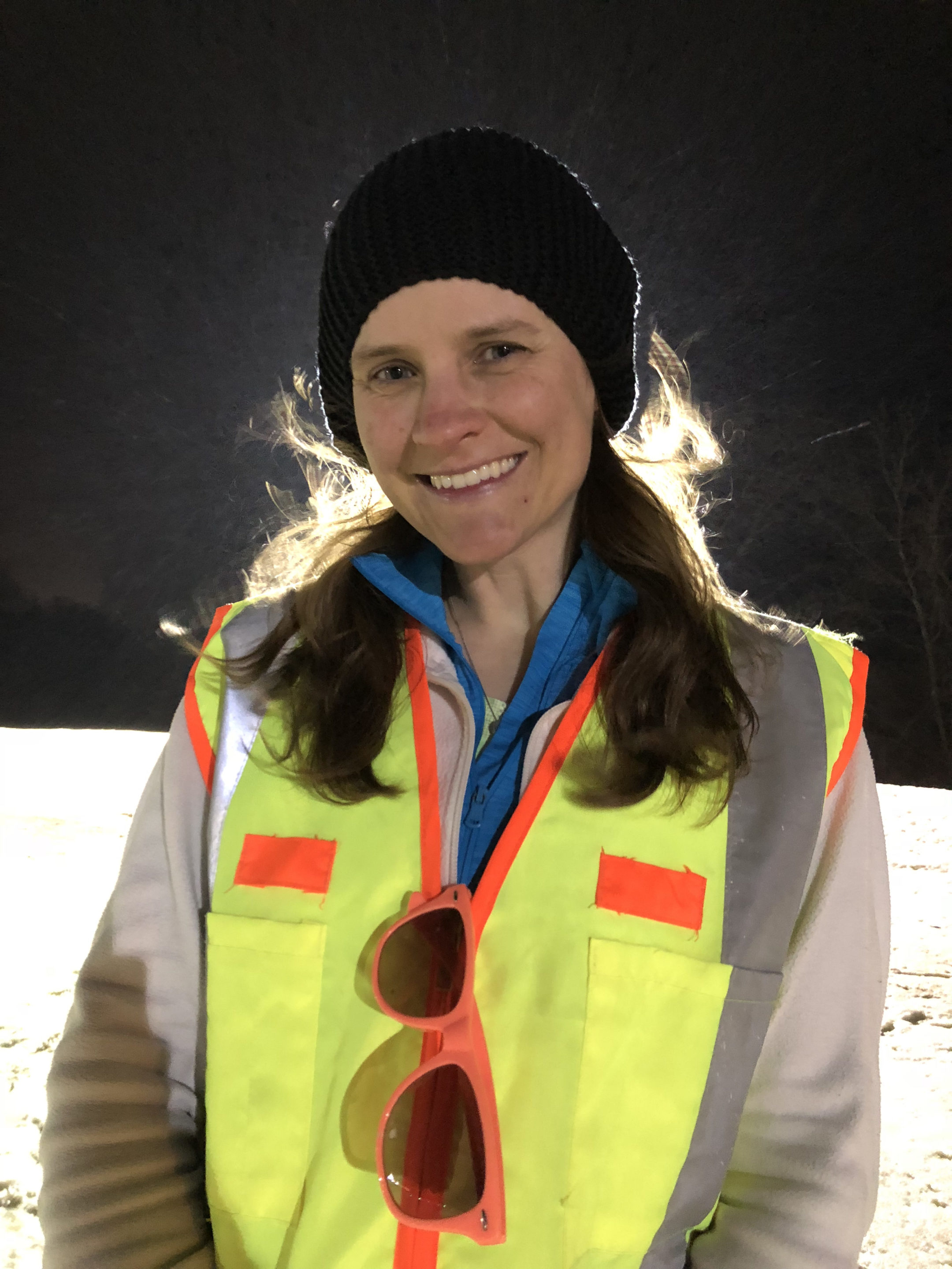 Photo of Braille Music Teacher wearing a bright yellow ski vest with orange reflective tape and a winer stocking cap.