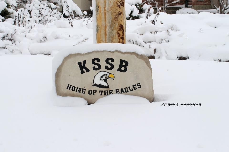 Stone Partially Covered In Snow With Eagle Head And KSSB Home Of The Eagles Carved On The Front.