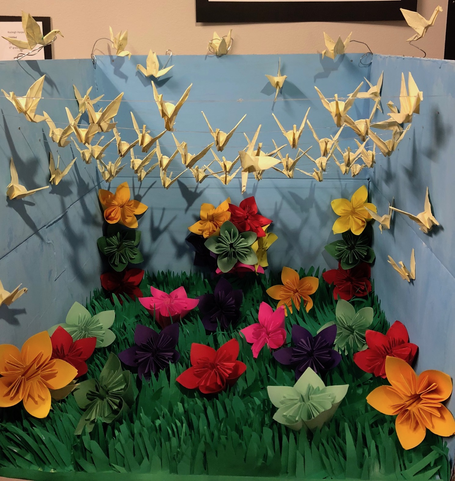 Origami diorama of flowers, grass and cranes.