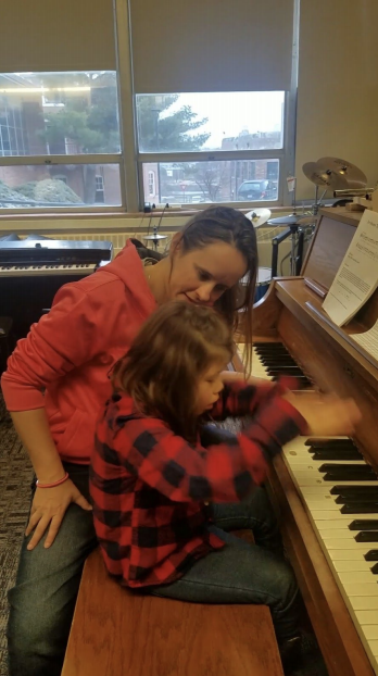 Student playing the piano while teacher sits next to her.