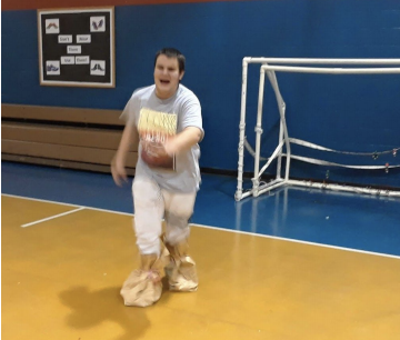 Student with paper bags on his feet as he pretends to ice skate across the gym floor.