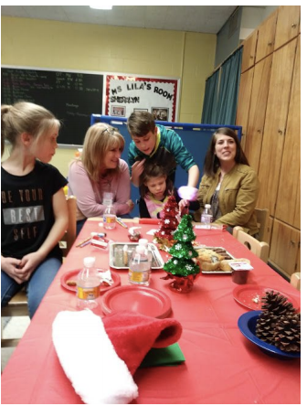 A student's mother, brother, sister and grandmother are sitting/standing at a table decorated with holiday decor and trays of cookies/treats. The student's brother is helping her to open her gift.