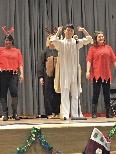4 students on the stage in costumes for winter concert.