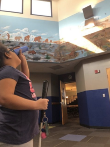 Student using a paper monocular to practice spotting an object at a distance. Student is looking at an exit sign that is above a large painted wall mural with scenes of animals such as gorilla, elephant, etc.