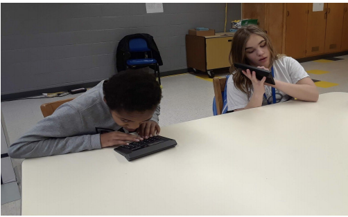 Two students sitting at a table using their talking calculators.