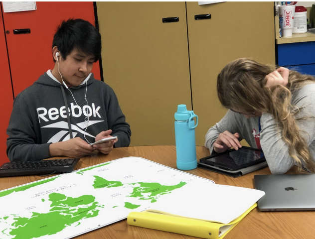 2 students sitting at a table with a tactual map of the world. One stuent using iphon and other using ipad.