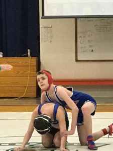 2 students in opening wrestling position. 1 student with hands and knees on the mat. The second wrestler by his side with one hand at opponents elbow and other hand around opponents waist.