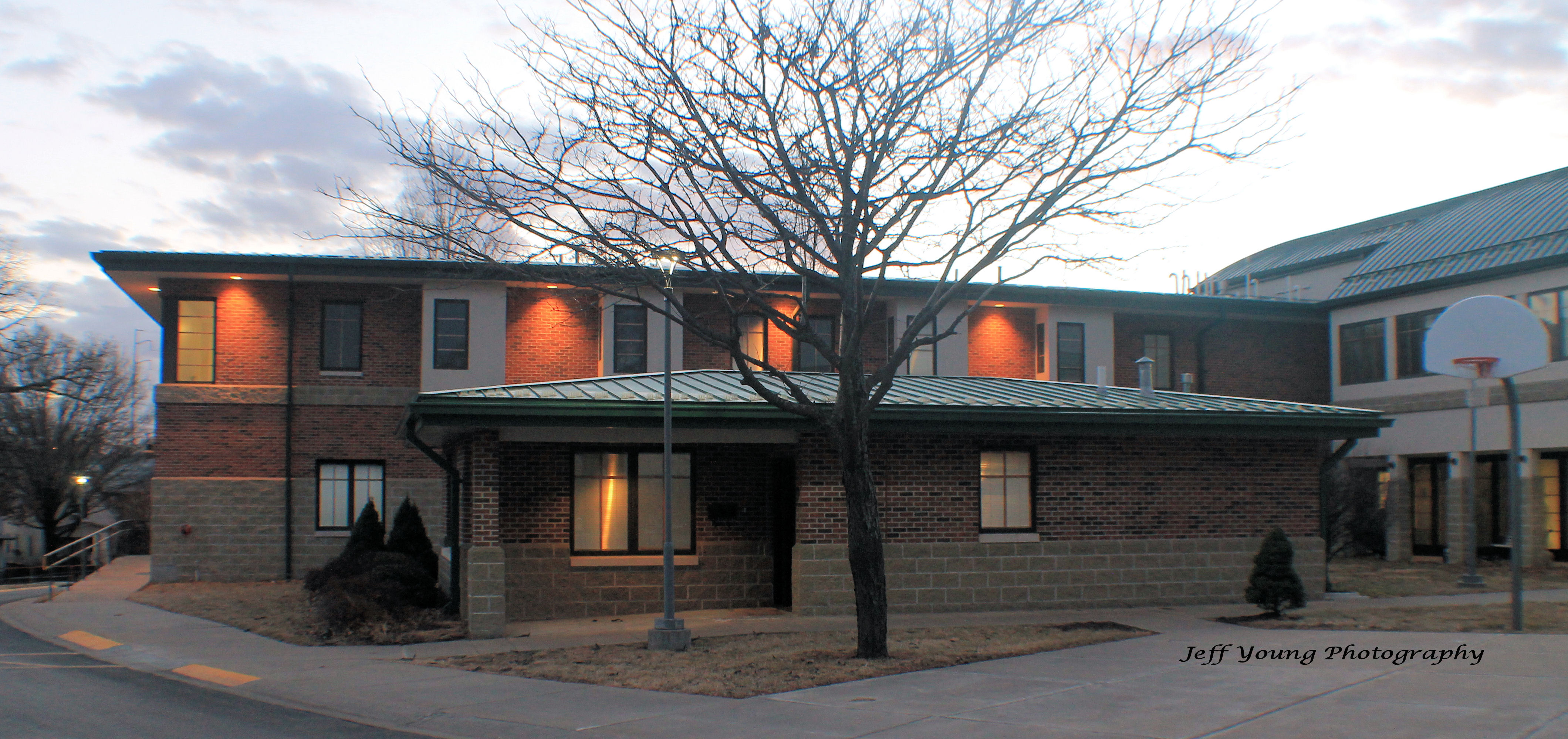 Two story brick building with a large tree, empty of leaves and a light pole in front. Night Lights beam from the 2nd story eaves shining orange in the sunset.