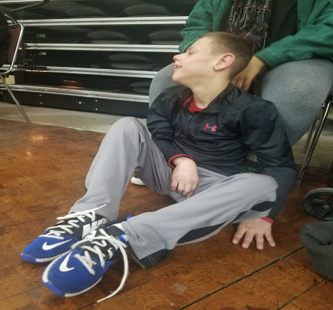 A student in sitting on the floor and using his left hand to feel the vibrations from the Tuba through the floor.
