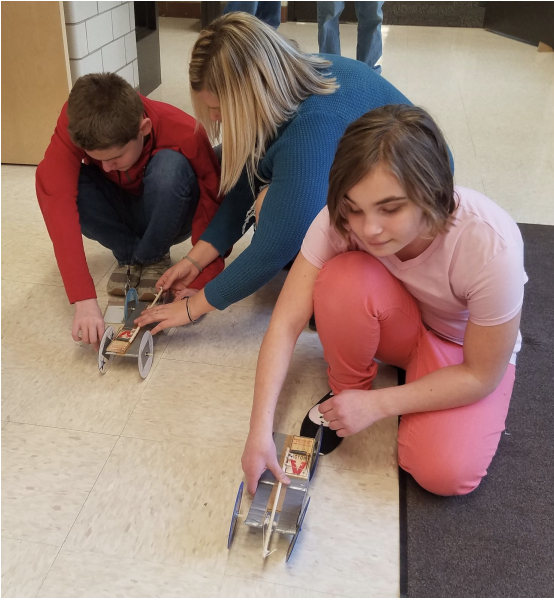 Two student sitting on classroom floor to launch their hand made mouse trap cars.