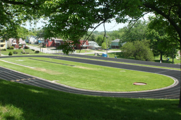 View of Track framed by two large trees to the right and left. The pond and homes are seen in the background.