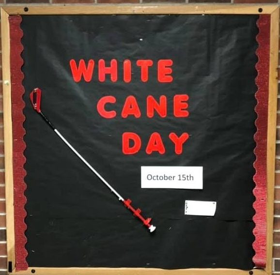 Bulletin Board With Words: White Cane Day And A Small Kiddie Cane Attached.
