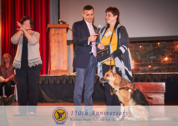 On a stage with a female using ASL Sign language on the left. In the center is Jon Harding holding a microphone for KSSB Alumni President who is speaking and reading from her braille note. He german shepherd dog guide seated on her left.