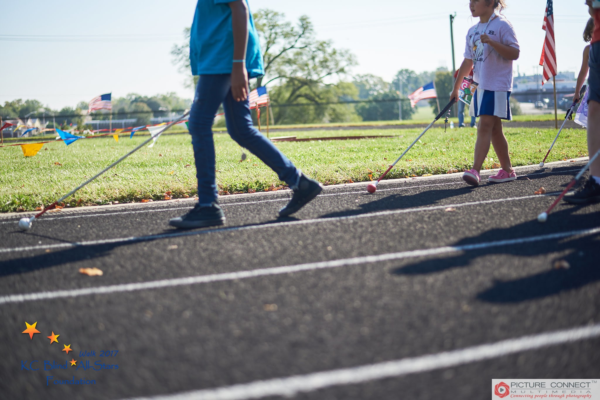 3 students walking with their canes on the KSSB track.