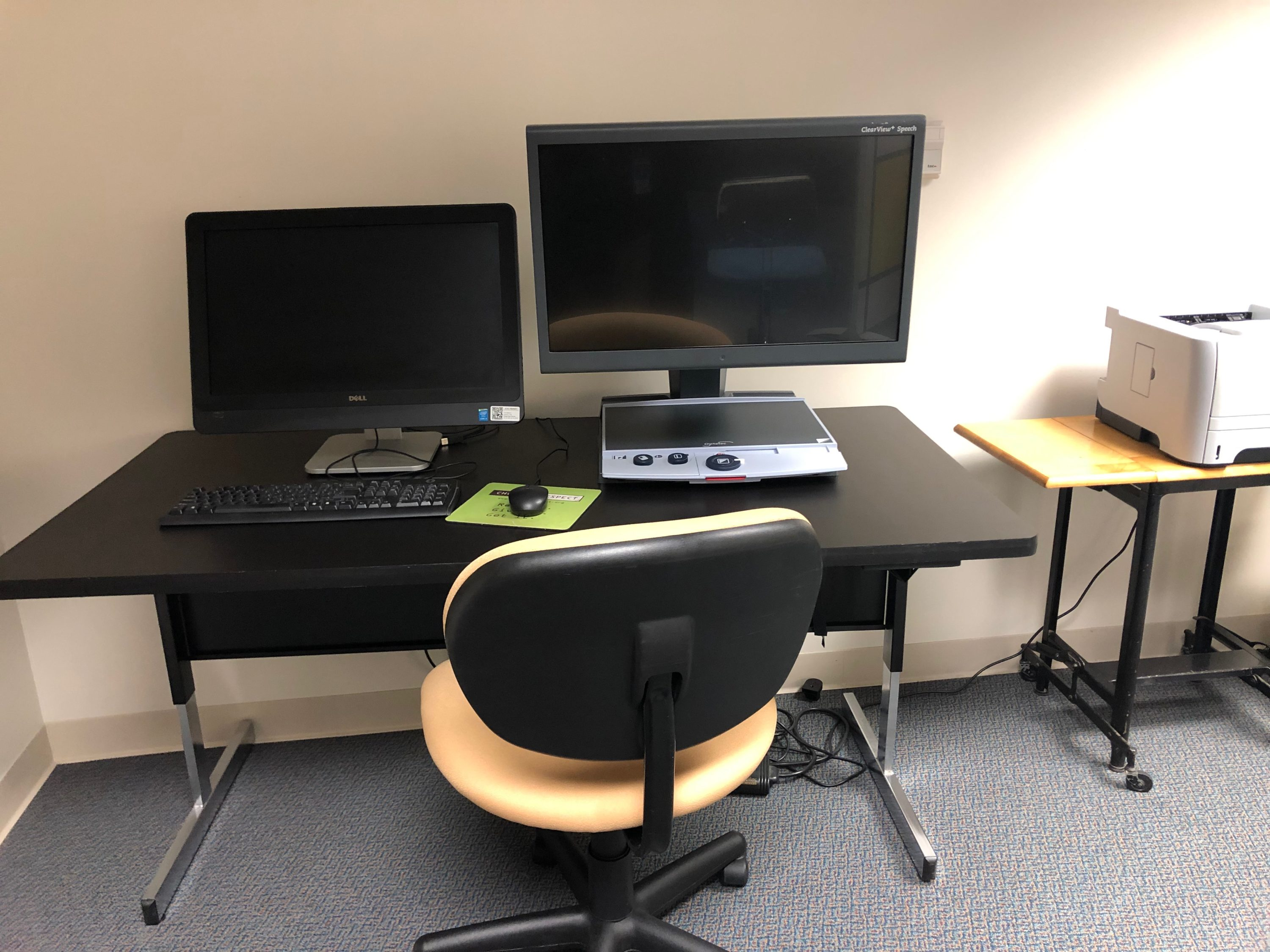 A table with a computer and a CCTV. To the right is a table with a printer.