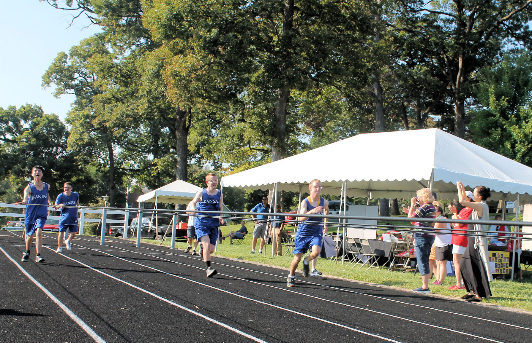 4 male students wearing blue track uniforms are racing on the track.
