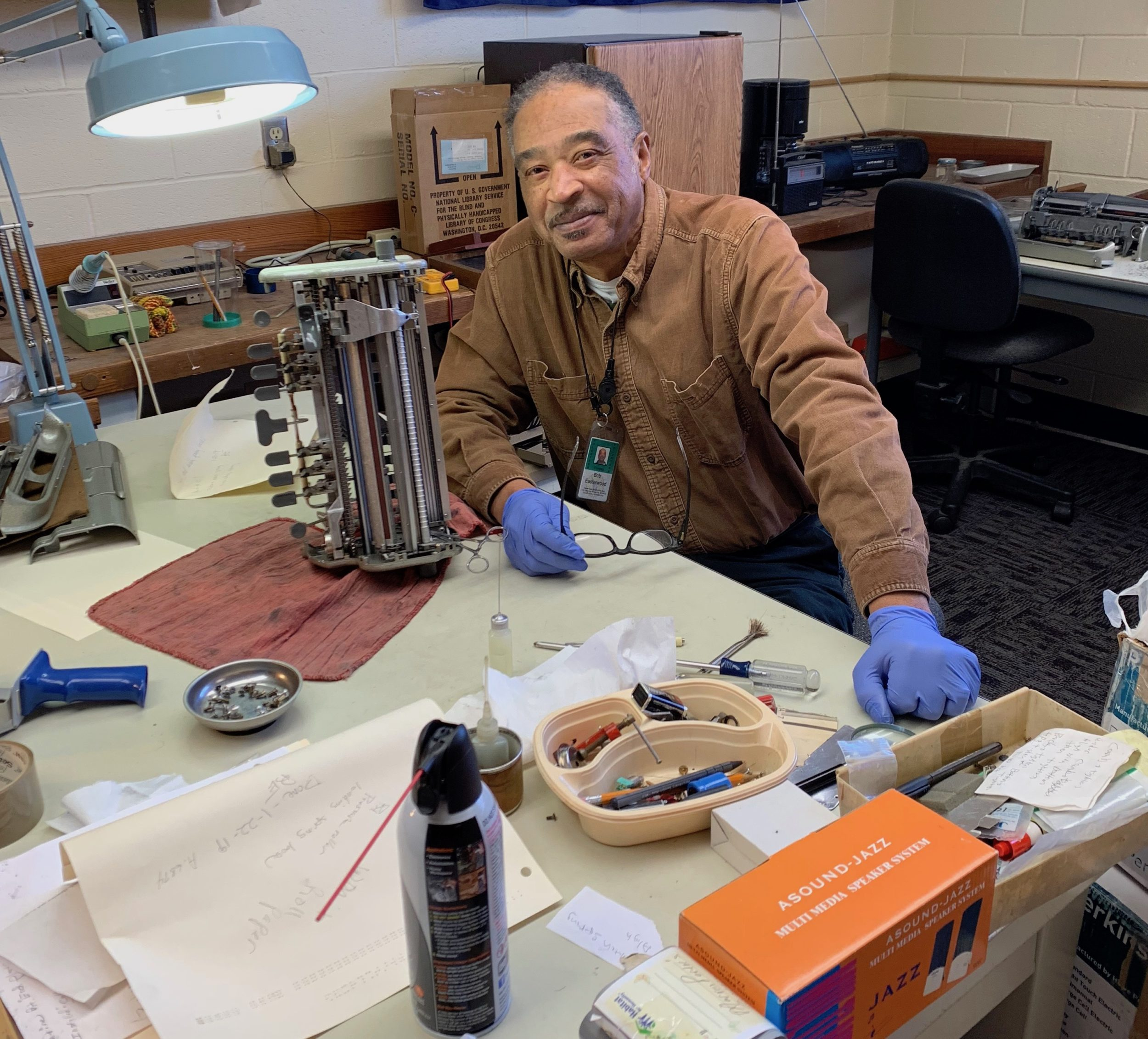 A Telephone Pioneer wearing a brown shirt and blue plastic work glove and sitting in front of a table containing the inner workings of a braille writer and tools.