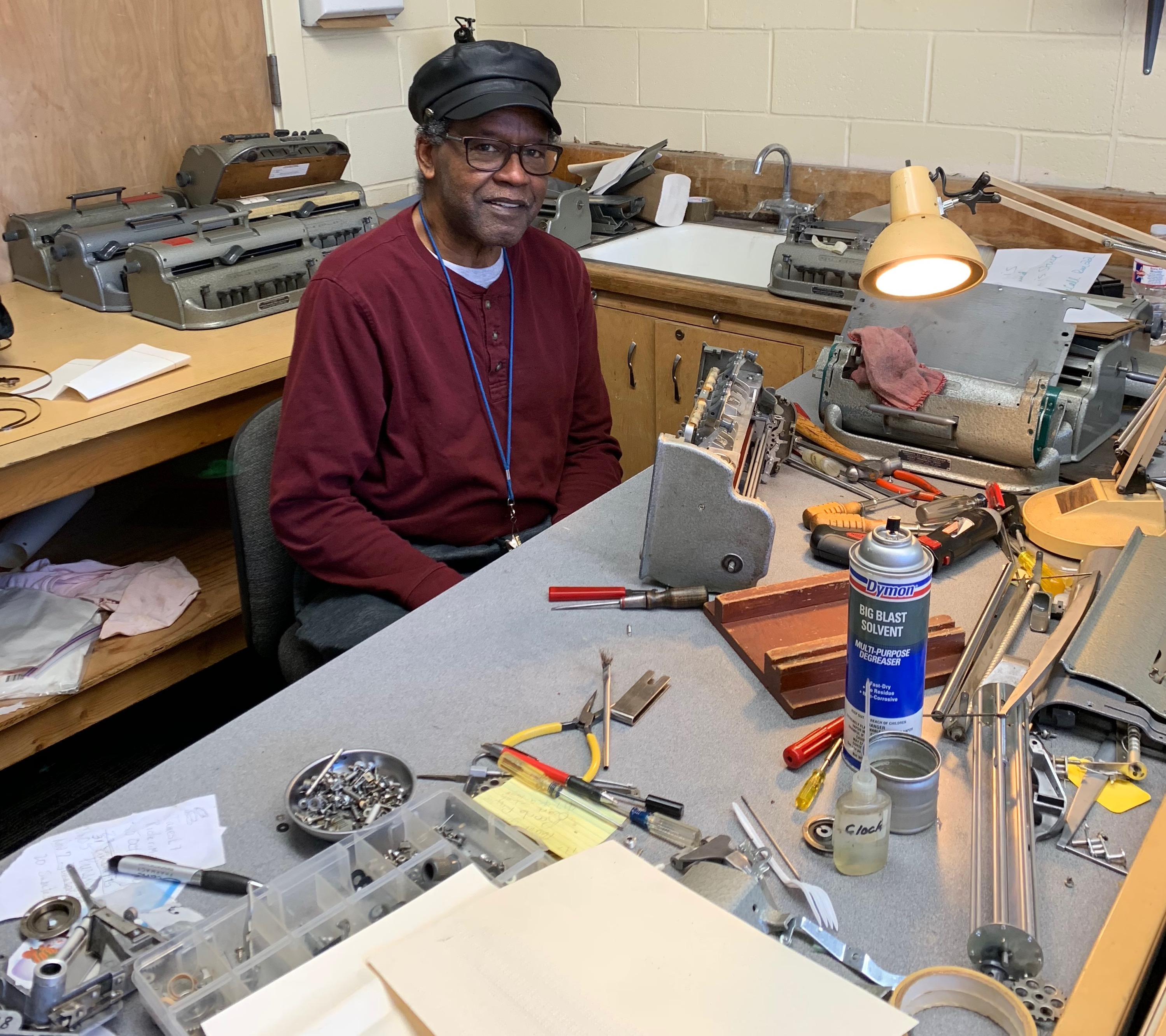 A Telephone Pioneer wearing a maroon shirt and a black leather baseball style cap sitting in front of a work table filled tools to repair braille writers.