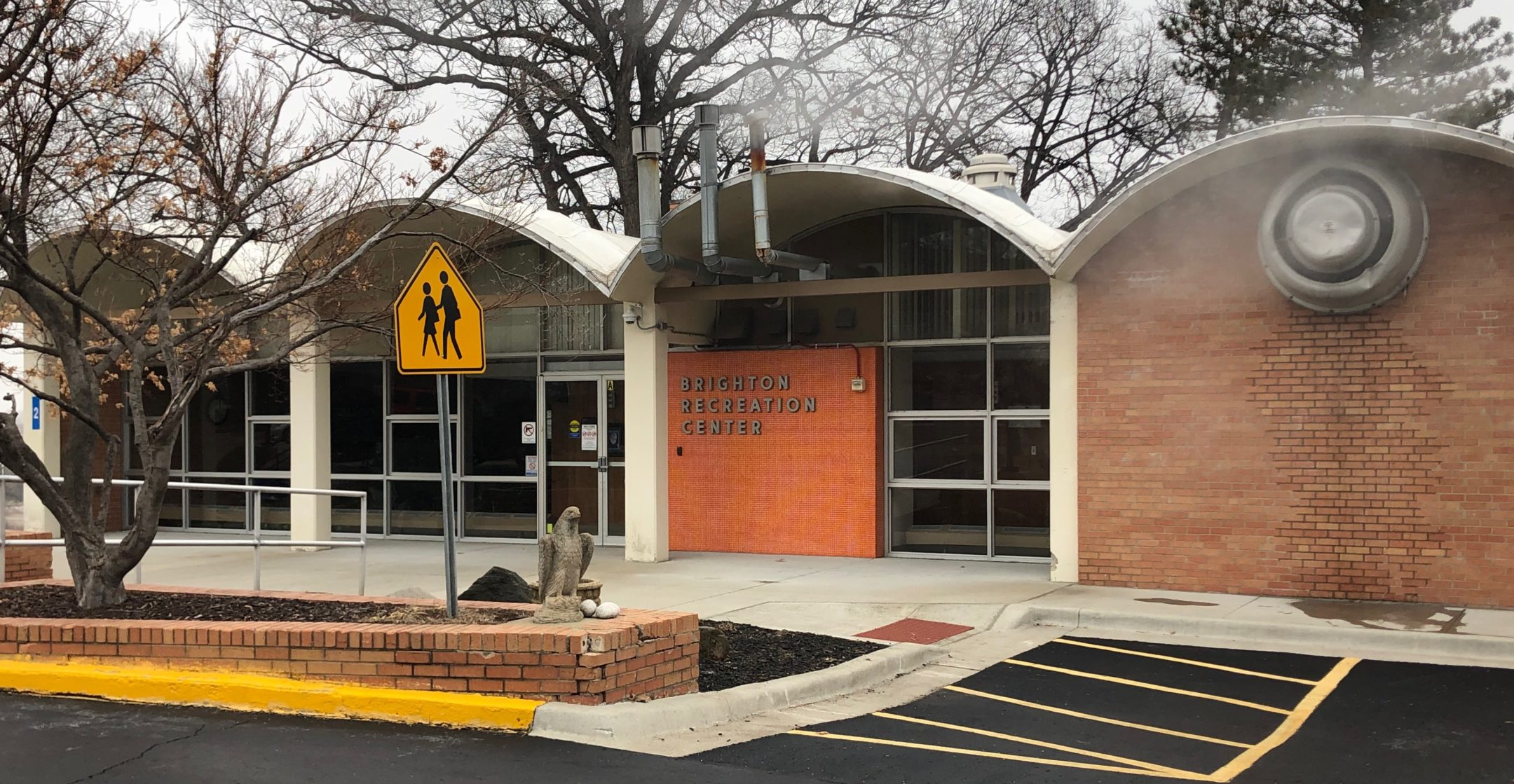 A building with 4 archway style awnings attached to white pillars. Most of the font wall is made with top to bottom windows. Under one awning is red brick wall with a heater vent creating fog into the air. An orange sign to the right of the entrance doors saying Brighten Recreation Center.