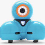 A small blue robot on wheels. A round ball with one circle shaped eye framed in orange is on the head of the robot. The neck is a black triangular shaped black bib with a small white and light blue triangle in center. Two ball shapes on wheels with flat bottoms for the legs directly under the head.