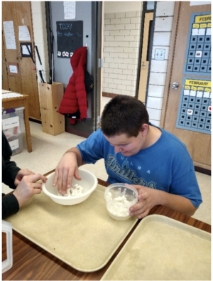 A student sitting at a table with right hand in a white plastic bowl and left hand holding a smaller clear plastic bowl.