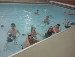 Several students swimming in the pool. A couple of students making faces and laughing for the camera.