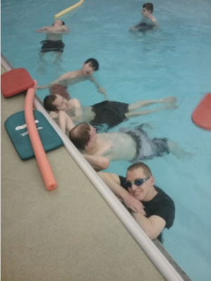 Students in the pool. On the edge are kickboards and pool noodles.