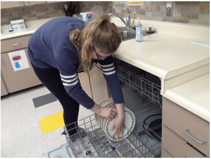 A female student with long hair in a pony tail and glasses is putting plates into a dishwasher.