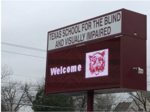 A large red entrance sign that says, Texas School for the Blind and Visually Impaired, Welcome.