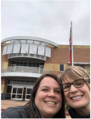 A selfie of 2 field service people with the entrance to the Texas School for the Blind in the background. Above the entrance door are large white smooth rectangle stones with braille letters t s b v i carved into them.