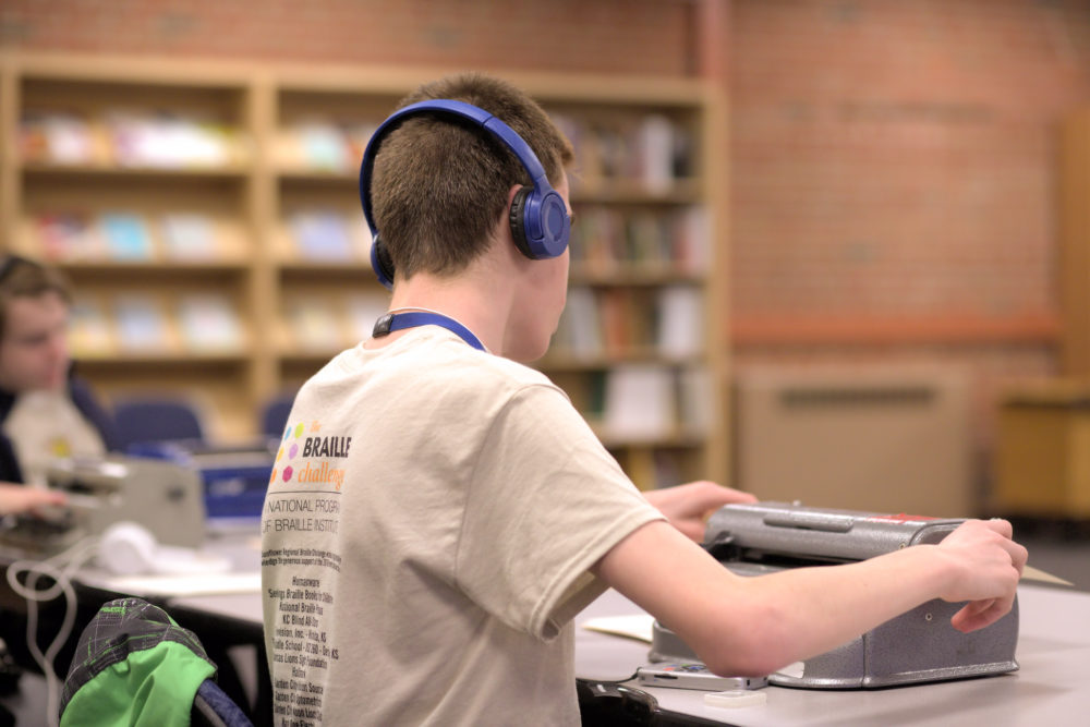 A male student with back to camera sitting at a table with a braille writer in front. He is wearing headphones and the 2019 braille challenge t-shirt. Bookshelves on the wall in the background.