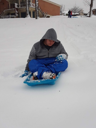 A student wearing heavy winter coat and mittens sitting in a sled and moving down a snow covered hill.