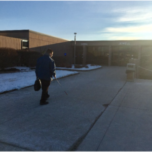 A view of a student walking toward the campus in the early morning light.
