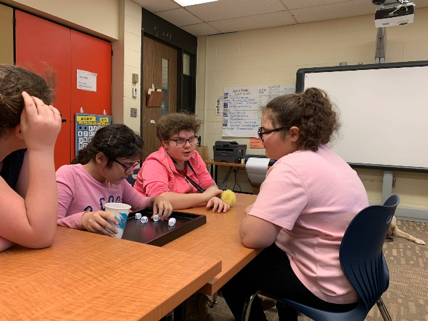 4 female students sitting around a table with a black wooden tray with 4 braille dice in center.