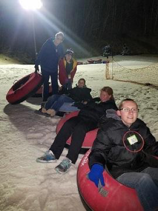 5 students in red snow tubes lined up in a single row. The sky is dark and beams of light illuminate the area from a single pole.