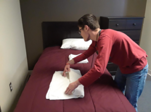 A student standing at bed with a white towel lying flat as he uses two hands at each near corner as he starts to fold the towel.