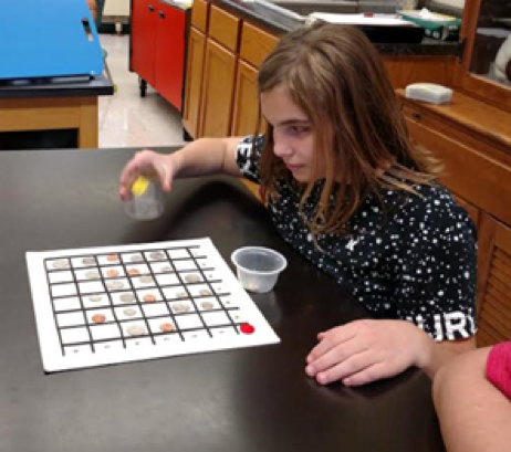 A Student Sitting At A Table With A Bingo Card In Front Of Her.