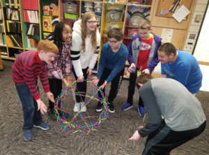 7 students in the library standing around a Hoberman sphere expandable ball.