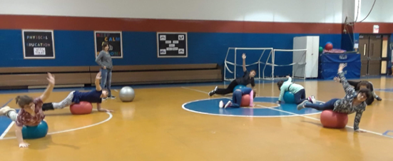 6 students in the gym lying on exercise balls with one arm on the floor and one arm raised to the ceiling. Body extended over the exercise balls so they are balancing on their stomachs.