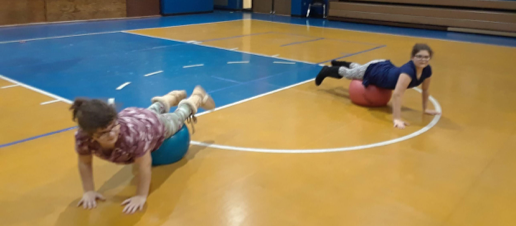 2 students in the gym lying over the top of large plastic exercise balls. Elbows bent and resting on the floor, heads up and body extended so that knees over the exercise balls.