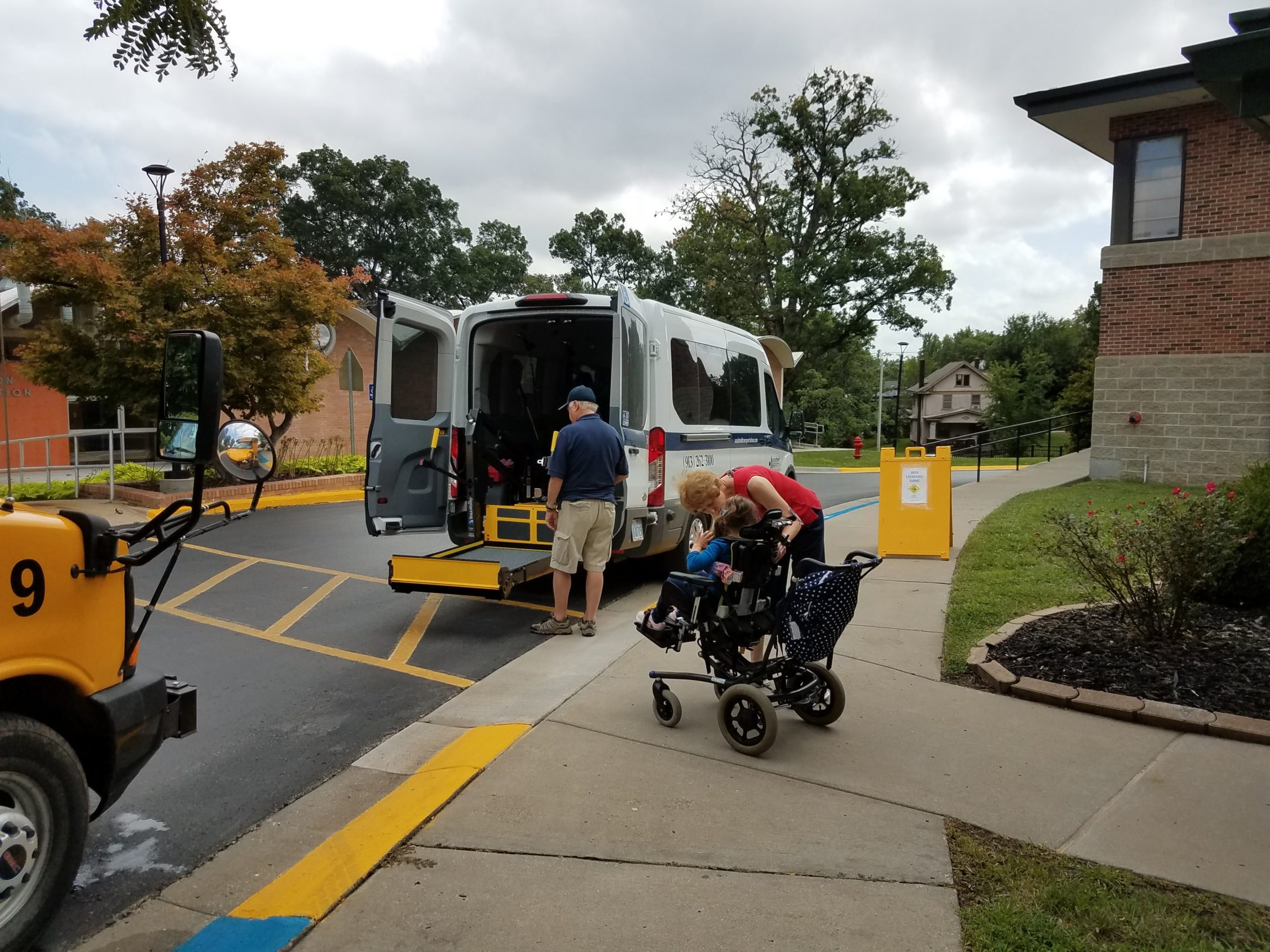 A white van with wheelchair lift parked in front of yellow cross walk between Recreation Building and Edlund Hall. A student who is in a wheelchair is waiting with teacher in red shirt to board the van. The front hood of a yellow bus is partially seen at the crosswalk.