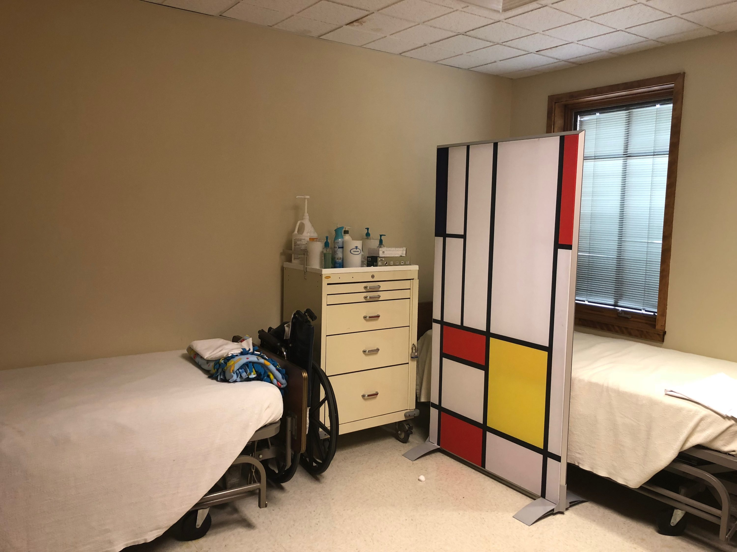 Health Center Sick Bay contains 2 medical beds on wheels with white sheets. A wheelchair is folded between the foot of one bed and a medical cart. Squares of white, red and yellow plexiglass bordered by navy blue stripes create a 5'x3' screen. The screen is on the side of the second bed.