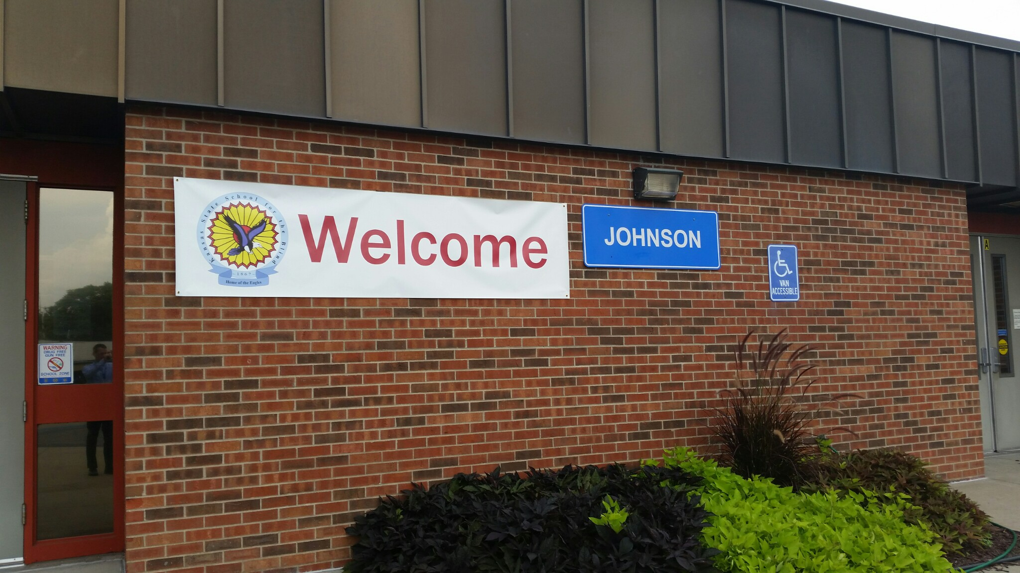 a close up of a red brick building with a printed white banner that says Welcome and the KSSB logo. A blue plastic large name plate that says Johnson.